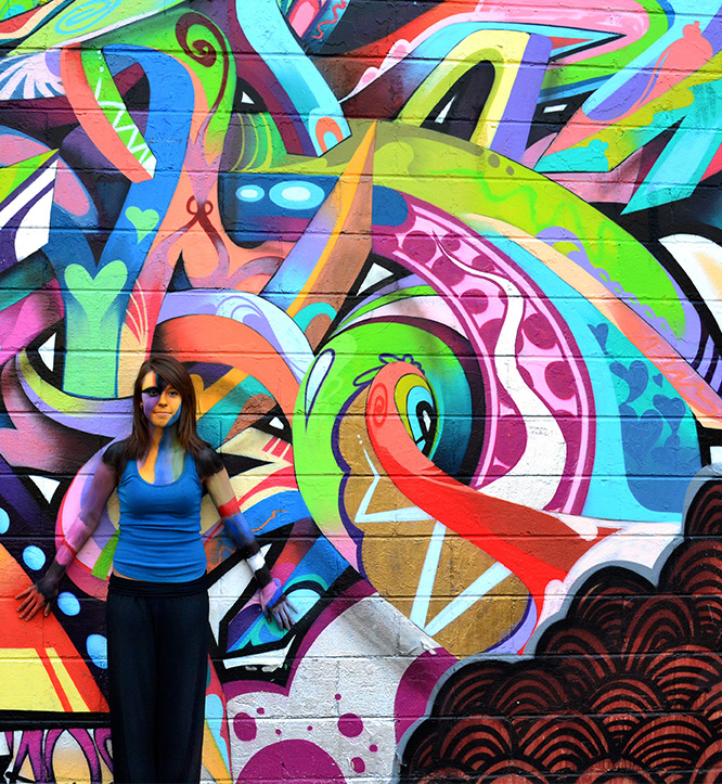 Girl standing next to wall art