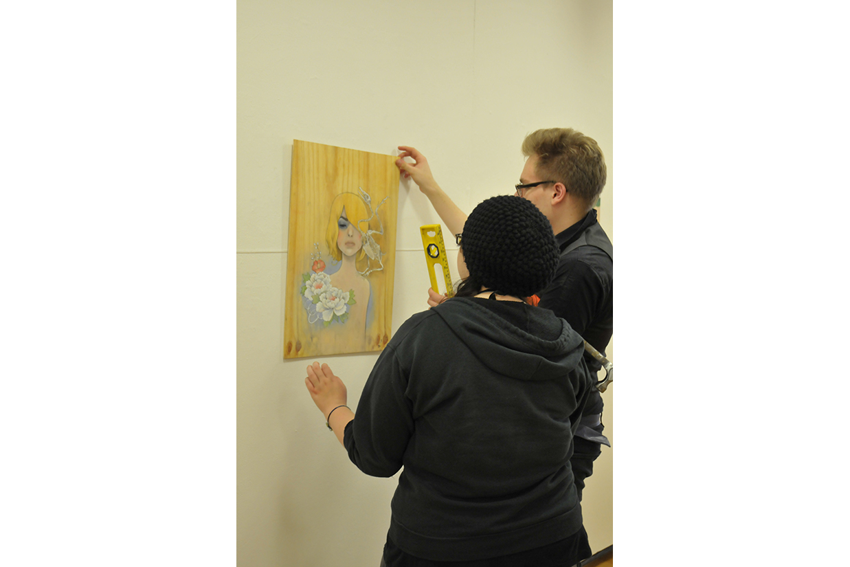 Students hanging art in gallery